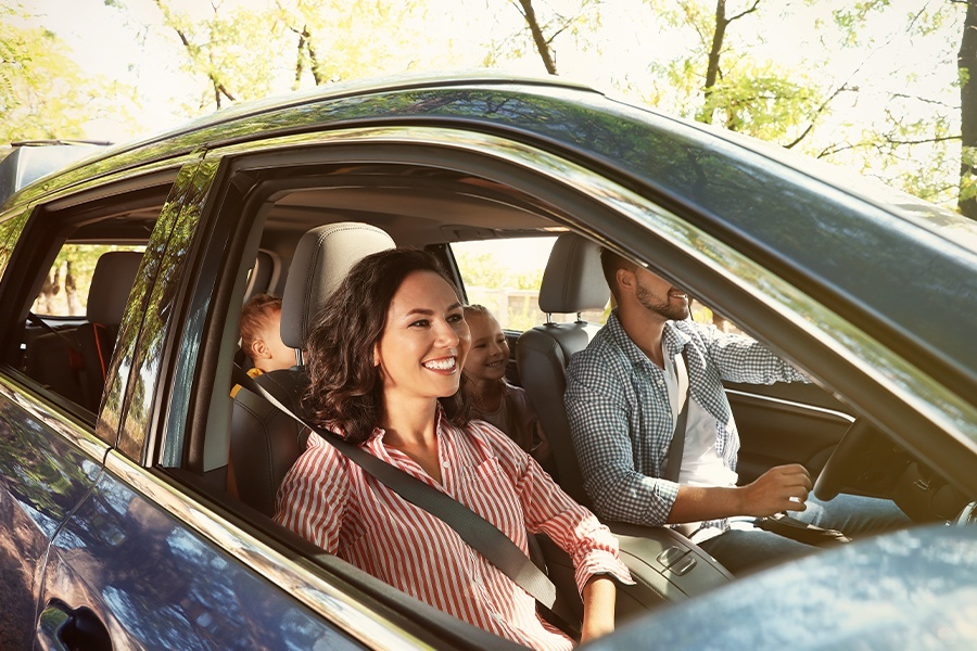 Personal Insurance - Happy Family Driving in a Car on a Road Trip on a Bright Sunny Day